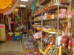 An inside look at a sari and puja store featuring saris, statues of Hindu deities, bottles of clarified butter, and cubes of camphor.