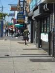 A teen dribbling his basketball along Liberty Avenue.